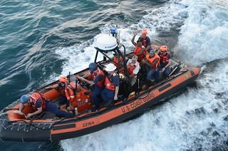 "A crew member from the fishing vessel El Apache waves good-bye to the crew of the Coast Guard Cutter Boutwell as he is transferred to a waiting Panamanian Coast Guard vessel. The El Apache's crew, reported overdue on its voyage to Panama City, Panama, Dec. 28, were rescued by the crew of the Boutwell, approximately 100 nautical miles southwest of Panama. The four fishermen, whose names will not be disclosed, were given food and water, clean clothes, showers, and phone calls home. ""Thank God! We shared a lot of joy that we were saved,"" said one of El Apache's crew. ""We are very thankful that we were picked up, after so many ships had passed by without seeing us."" Coast Guard photo by LT. j.g. Eric Balcunas"