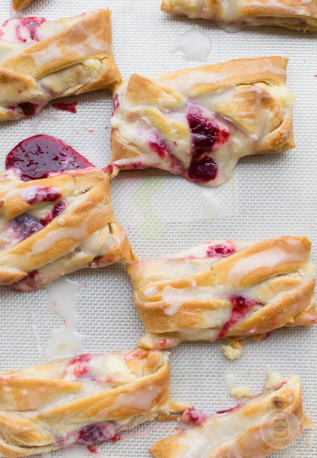 raspberry cream cheese danish braid cut into pieces on baking mat oozing raspberry juices