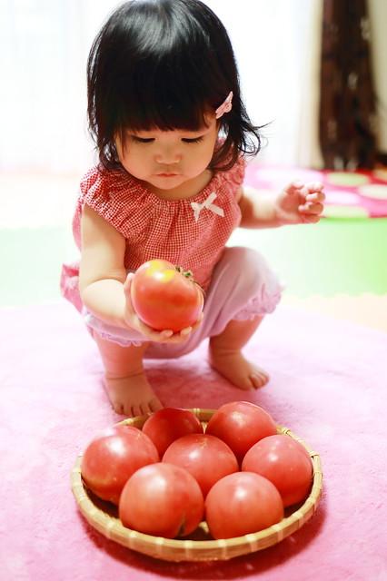 Baby selecting tomato