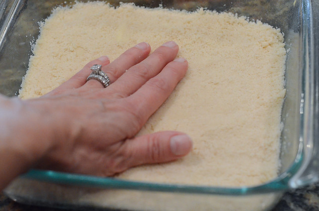 A hand presses dough down into a baking dish.
