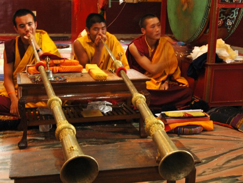 Tibetan monks playing long horns propped up on a table, beating the big green leather drum, prayer books on a pillow, Sakya Lamdre, Tharlam Monastery of Tibetan Buddhism, Boudha, Kathmandu, Nepal by Wonderlane