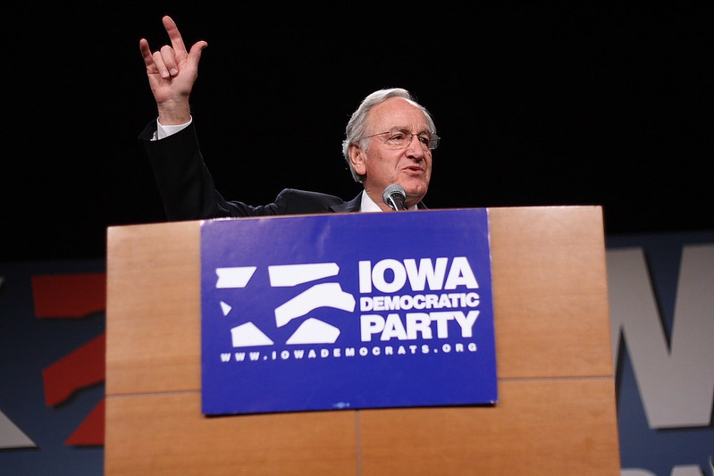 "Senator Tom Harkin (D-IA) signs ""I love you"" as he approachest the podium"