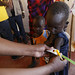International Rescue Committee staff measure the upper arm circumference of 7-year-old Ngikadelio Ngikeny as part of a malnutrition screening programme, at a health clinic in Turkana County, northwest Kenya, 29 March 2017.
