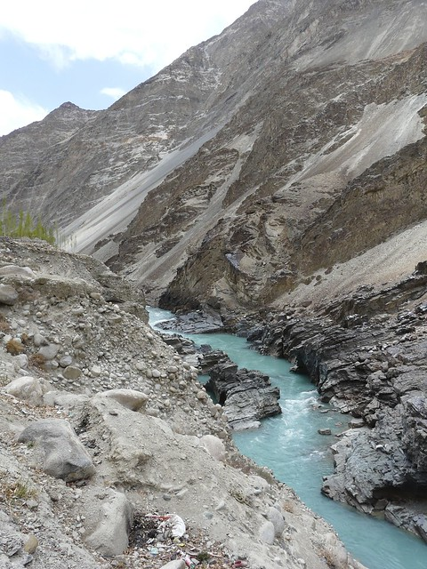 A bright blue Indus flowing through a rocky gorge