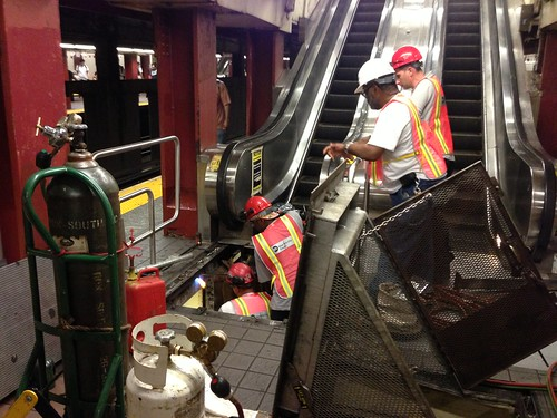 Repairing the escalator, 34th St., Manhattan