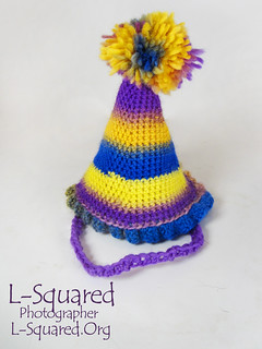 cone-shaped party hat crocheted with yellow, purple and blue yarn.