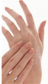 Woman rubbing hand cream on her hands