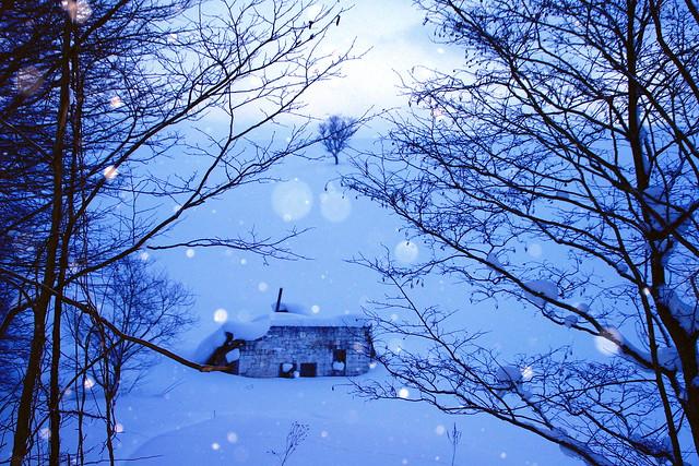 雪降る廃屋のある丘