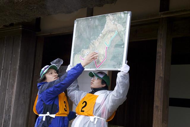 ボードを使って草を刈る場所や諸注意などを説明する白川学芸員.