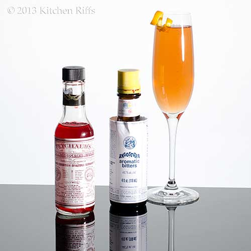 Seelbach Cocktail with bottles of Peychaud's and Angostura bitters