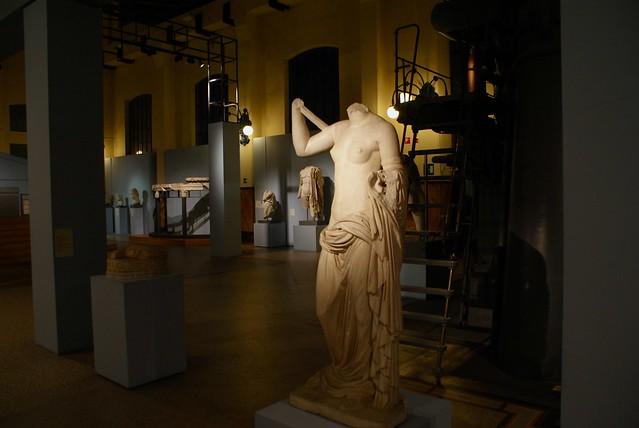 Une buste féminin devant des machines industrielles.