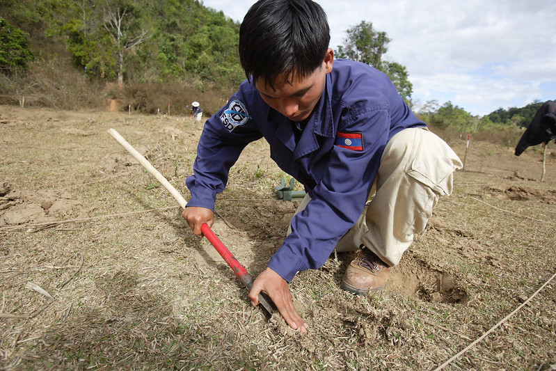 FSD deminer Mr Dasone Sitthipone working with a detector at a UXO clearance area, begins excavating an unidentified object.