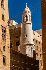 Power lines, mosque minaret and buildings made of adobe mud - desert city of Shibbam