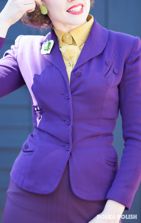 Royal purple 1940s suit with decorative pockets paired with chartreuse blouse and accessories