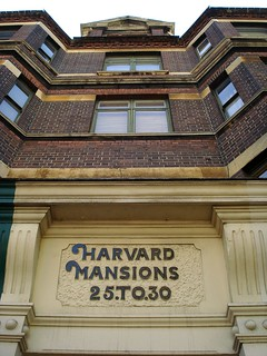 A view looking up at the upper floors of a brick building, taken standing quite close to the building.  Windows are inset at intervals.  A bas-relief near the bottom of the photo reads 'Harvard Mansions 25 to 30'.