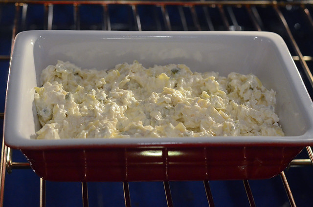 The artichoke dip is placed in the oven.