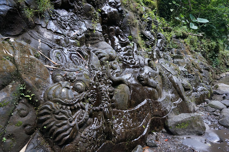 Sculpture in the rock face by the Ayung river, Bali.