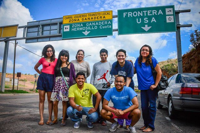 "Eight immigrant youths stand in front of a highway sign that reads ""frontera"""