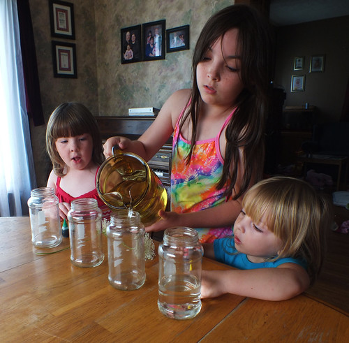 Julia fills the jars with water.