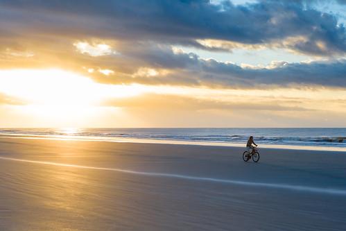 ocean sky woman usa sun beach sc water bike bicycle clouds race sunrise person us sand ride unitedstates streak unitedstatesofamerica southcarolina footprints places riding chase locations flee kiawahisland ef2470f28lusm