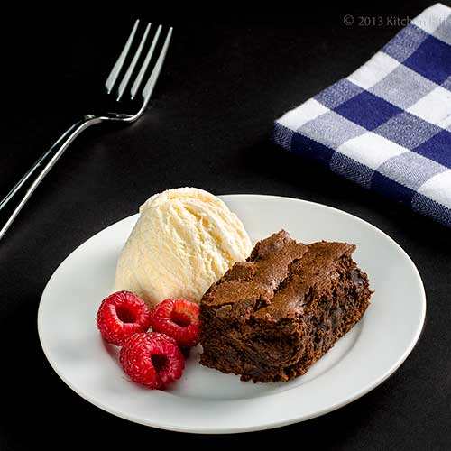 Chocolate Mascarpone Brownies on plate with vanilla ice cream and raspberries
