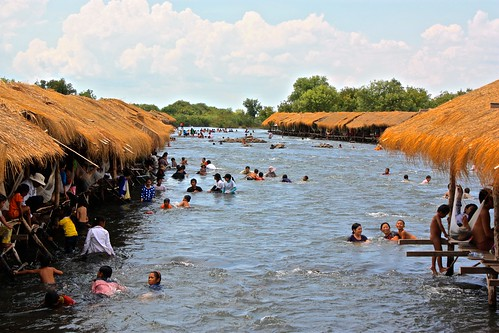 Just outside of Kratie, locals enjoy these thatched roof shacks on the river as they get a massage from rapids on the Mekong