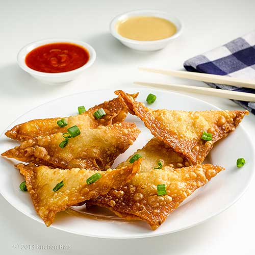 Crab Rangoon on plate with dipping sauces in background