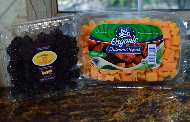 A container of chopped butternut squash and a container of blackberries.