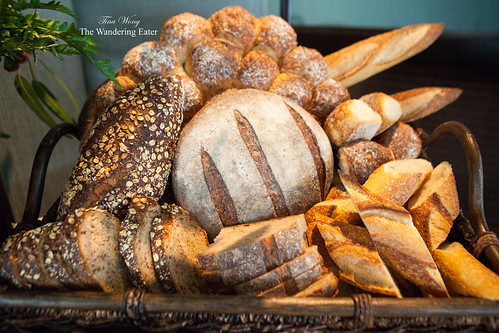 Bountiful bread basket of Rosemary focaccia, baguette, and sliced dark rye sourdough