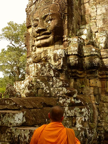Monk watching famous faces of Bayon temple