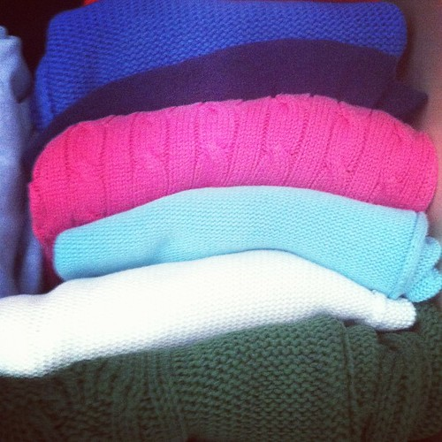 #folded knit pullovers on my closet shelf.