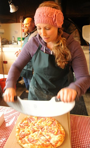 Young woman cutting a Hawaiian pizza with a pizza blade, wearing a wide crocheted pink hair band, West Olympia, Washington, USA by Wonderlane