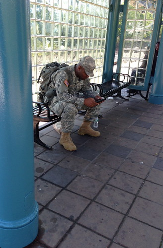 A soldier, waiting for the light rail
