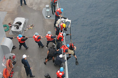 Crew members aboard USS Pearl Harbor (LSD 52) recover a bale of marijuana found adrift in the Pacific. (U.S. Navy photo)