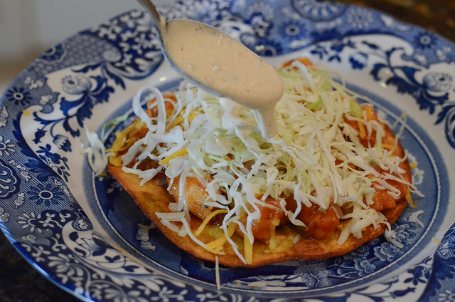 Ranch dressing is drizzled from a spoon over the top of a tostada.