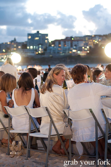 Guests dining as dusk falls at Diner en Blanc Sydney 2013 Bondi Beach
