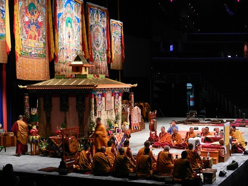Tibetan Buddhist monks of the Gelugpa order pray and make offerings in front of the Kalachakra Pavilon, thangkas of Kalachakra, Lord Buddha, mandala, Verizon Center stage, throne, drums, silks, decorations, Kalachakra for World Peace, Washington D.C., USA by Wonderlane