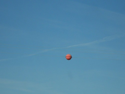 A red balloon-like objet suspended on a wire, in front of an expansive sky, peckered with clouds.