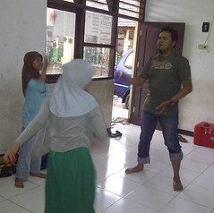 Yanuar juggling with two Red Nose students