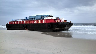 Towing vessel PUSHY had lost control of a 125-foot deck barge it was towing following an interaction with a large swell off of Atlantic Beach, N.Y. After the towing vessel and deck barge separated, the vessel sank and the barge was pushed up onto the beach at Silver Point County Park, where its owners, under Coast Guard supervision, are devising a plan to safely remove the barge. U.S. Coast Guard photo.