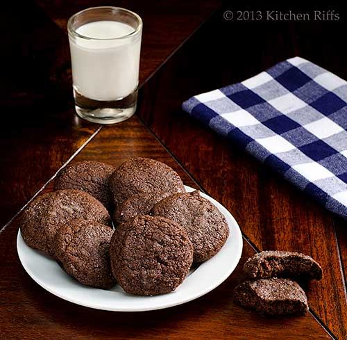 Double Orange Dark Chocolate Cookies on plate, with milk and napkin in background