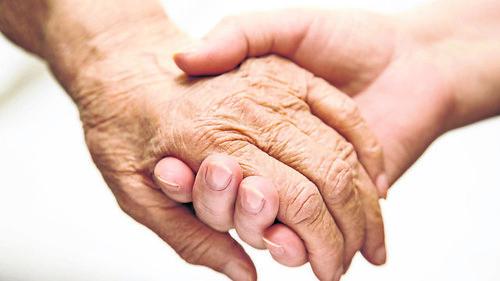 Adult Helping Senior In Hospital