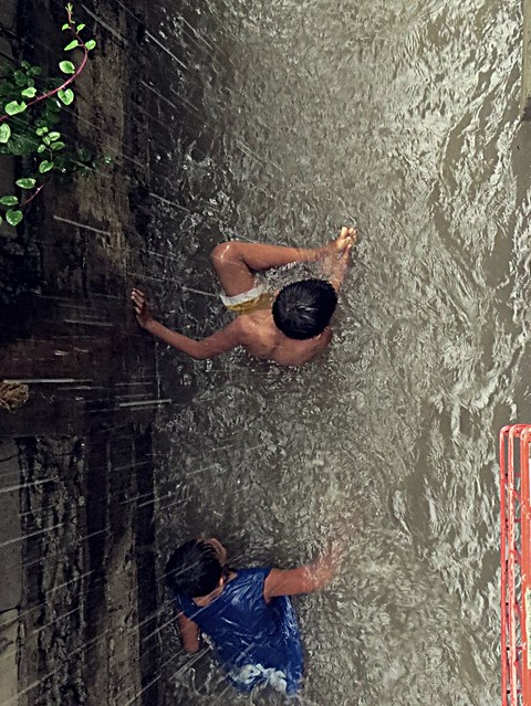 A young boy checking his foot, as he felt he stepped on something while playing in the flood.  Photographed by Bernard Eirrol Tugade