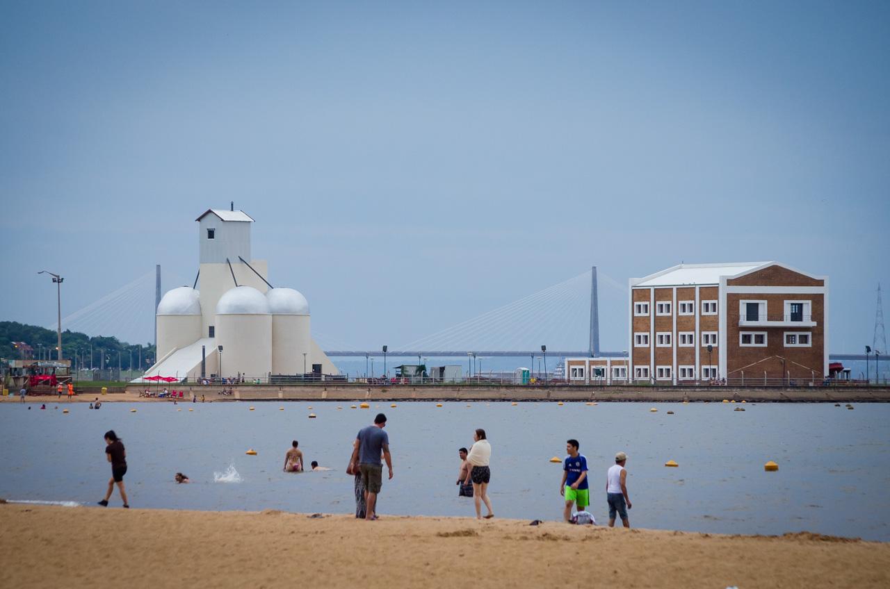 Turistas se dispersan por la playa San José de Encarnación en el Sábado Santo, a pesar de las bajas temperaturas muchos optaron por bañarse en las aguas del Paraná, al fondo se puede ver los edificios históricos de Encarnación y el puente San Roque González que une con Argentina. (Elton Núñez).