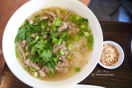 Large bowl of Tom-Yum Pork Leg Soup with crushed peanuts