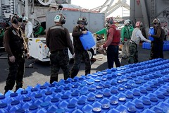 Sailors pass containers of fresh water which will be loaded onto helicopters aboard the aircraft carrier USS George Washington (CVN 73) and transported ashore in support of Operation Damayan. (U.S. Navy photo by Mass Communication Specialist 3rd Class Peter Burghart)