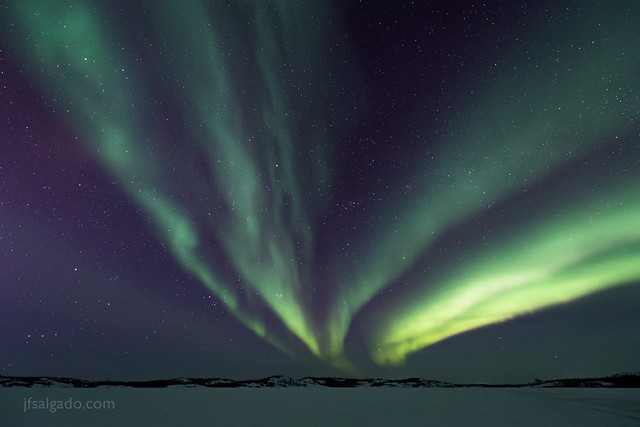 Multiple aurora curtains over a frozen lake