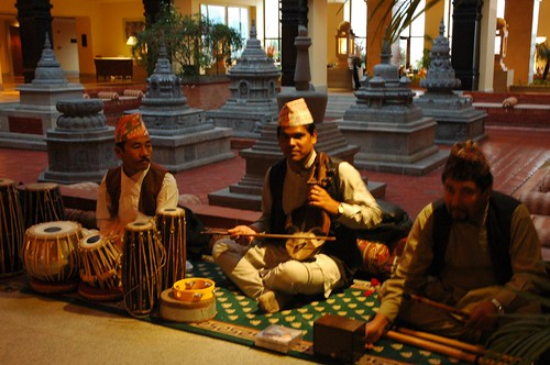 Nepalese band, traditional music, tabla (drums), violin, flutes, Tibetan Buddhist style stupas in the background (marble), lobby, Hyatt Regency Boudha, Kathmandu, Nepal by Wonderlane