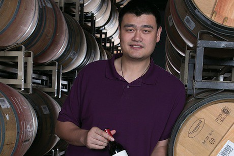 August 2013, 2013 - Yao Ming stands in front of wine barrels at his winery