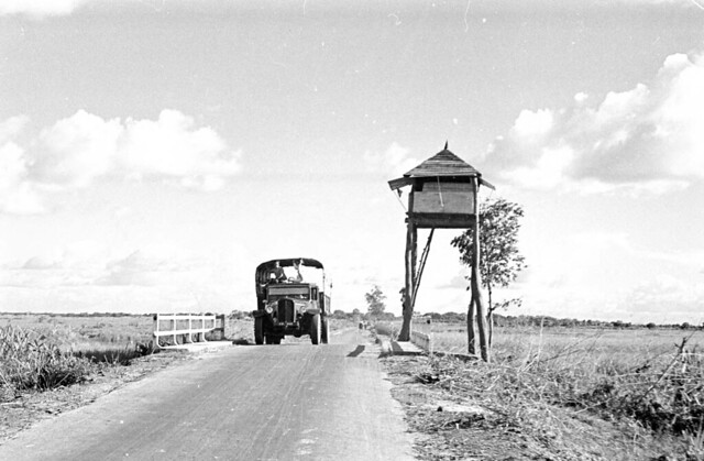 1950 Truck passing watchtower on stilts in Tây Ninh